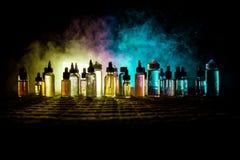 Concepto de Vape Nubes de humo y botellas líquidas del vape en fondo oscuro Efectos luminosos Útil como anuncio o del fondo o del fotos de archivo libres de regalías