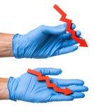 Concepto de ventas descendentes, reduciendo el riesgo de enfermedad El doctor en guante azul sostiene una flecha roja abajo en su Fotografía de archivo