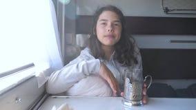 Concepto de viaje por ferrocarril. Niña en la ventana toma té comiendo galletas en un vagón de tren compartimentado. Morenita d metrajes
