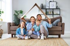 Concepto de vivienda y de relocalización padre y niños felices de la madre de la familia con el tejado en casa fotografía de archivo
