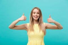 Concepto del éxito y de la forma de vida: Mujer alegre feliz joven que muestra el pulgar para arriba sobre fondo azul en colores  fotos de archivo