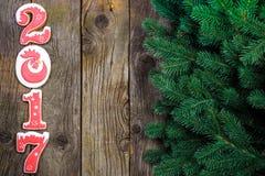 Concepto del Año Nuevo Cuadro 2017 del pan de jengibre, rama en un fondo de madera, espacio del abeto para el texto Fotos de archivo libres de regalías