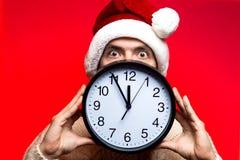 Concepto del Año Nuevo de la Navidad Hombre con el sombrero de Papá Noel que mira sca Foto de archivo libre de regalías