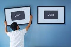 Concepto del Año Nuevo Hombre asiático que lleva a cabo un marco de 2018 en b Imagenes de archivo