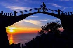 Concepto 2018 del Año Nuevo Hombre y bicicleta de la silueta en el puente Foto de archivo