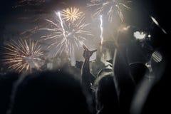concepto del Año Nuevo - muchedumbre y fuegos artificiales que animan Fotos de archivo libres de regalías