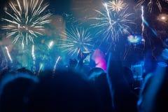 Concepto del Año Nuevo - muchedumbre y fuegos artificiales que animan Foto de archivo