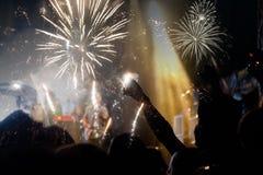 Concepto del Año Nuevo - muchedumbre y fuegos artificiales que animan Foto de archivo libre de regalías