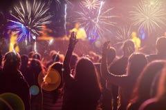 Concepto del Año Nuevo - muchedumbre y fuegos artificiales que animan Imágenes de archivo libres de regalías