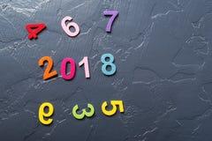 Concepto 2018 del Año Nuevo Números coloreados dispersados en fondo negro Fotos de archivo libres de regalías