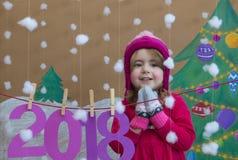 Concepto 2018 del Año Nuevo Pequeña muchacha hermosa que adorna el número del Año Nuevo fondo de un árbol de navidad pintado y Imagen de archivo