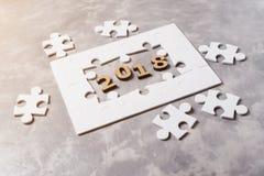 Concepto 2018 del Año Nuevo Rompecabezas en fondo concreto gris Fotografía de archivo