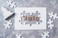 Concepto 2018 del Año Nuevo Rompecabezas en fondo concreto gris Imagenes de archivo