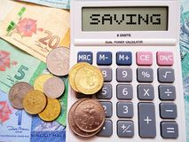Concepto del ahorro con los billetes de banco, las monedas y la calculadora foto de archivo libre de regalías