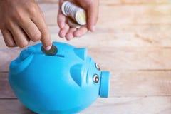 Concepto del ahorro del negocio o de las finanzas con la mano que pone la moneda en b imagenes de archivo