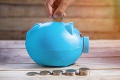 Concepto del ahorro del negocio o de las finanzas con la mano que pone la moneda en b imagen de archivo