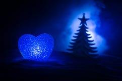 Concepto del amor del Año Nuevo Burning hermoso en diversa silueta del corazón de los colores y del árbol de abeto, en el fondo e Imagen de archivo