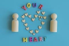 Concepto del amor Dos figuras de madera y un corazón en un fondo azul Figuras de madera del concepto dos del amor y un corazón en imágenes de archivo libres de regalías