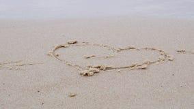 Concepto del amor Un corazón en el arena de mar y las ondas Primavera en el mar Báltico almacen de video