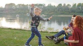 Concepto del amor y de la paternidad La familia feliz con los niños sopla burbujas de jabón al aire libre almacen de metraje de vídeo