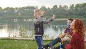 Concepto del amor y de la paternidad La familia feliz con los niños sopla burbujas de jabón al aire libre almacen de video