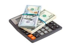Concepto del asunto Billetes de banco del dólar con la calculadora Fotos de archivo