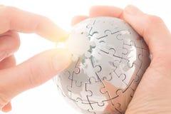Concepto del asunto con un globo del rompecabezas del edificio de la mano Fotografía de archivo libre de regalías