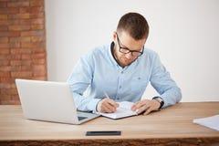 Concepto del asunto Director de sexo masculino sin afeitar maduro apuesto de la compañía en los vidrios y la camisa azul que trab imagen de archivo