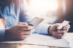 Concepto del asunto Hombre de negocios que sostiene el businesscard blanco de la mano y que hace smartphone de la foto Proyecto d Imagenes de archivo