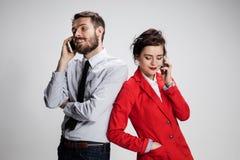 Concepto del asunto Los dos colegas jovenes que sostienen los teléfonos móviles en fondo gris Fotografía de archivo libre de regalías