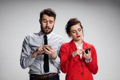 Concepto del asunto Los dos colegas jovenes que sostienen los teléfonos móviles en fondo gris Imagen de archivo libre de regalías