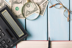 Concepto del asunto Lupa con los vidrios, los billetes de dólar, el cuaderno, la pluma y la calculadora en fondo de madera azul Imagen de archivo