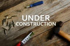 Concepto del asunto Martillo, cinta métrica, destornillador con y x22; DEBAJO DE CONSTRUCTION& x27; palabras en fondo de madera foto de archivo libre de regalías