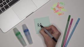 Concepto del asunto Mujer que escribe RUNK en la libreta adhesiva en lugar de trabajo de la oficina metrajes