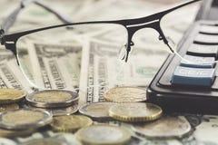 Concepto del asunto Primer de gafas cerca del dinero en billetes de banco del dólar con las monedas y la calculadora foto de archivo