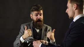 Concepto del asunto Sorprenda a un hombre en un traje del dinero visto Un dinero de juegos del hombre de negocios delante de otro almacen de video