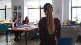 Concepto del asunto Un equipo de trabajo que tiene una conferencia Una mujer trae los documentos al equipo imagen de archivo