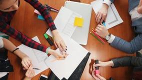 Concepto del asunto Un equipo del trabajo productivo que tiene una conferencia y que discute el diseño almacen de metraje de vídeo