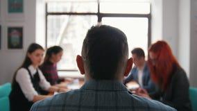 Concepto del asunto Un jefe que se sienta en la conferencia y que tiene una conversación con sus subordinados almacen de video