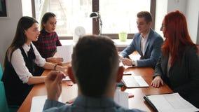 Concepto del asunto Un jefe que se sienta en la conferencia y que tiene una conversación con sus subordinados mientras que sostie almacen de video