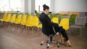 Concepto del asunto Una mujer en el centro de negocio consigue en el marco que se sienta en silla metrajes
