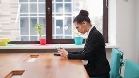 Concepto del asunto Una mujer en los auriculares que juegan al juego en su teléfono metrajes