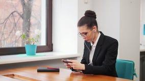 Concepto del asunto Una mujer en los auriculares que se sientan por la tabla y que juegan al juego en su teléfono almacen de video