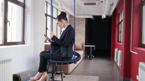 Concepto del asunto Una mujer que se sienta en los oscilaciones en la oficina y escuchar la m?sica almacen de video