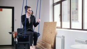 Concepto del asunto Una mujer que se sienta en los oscilaciones en la oficina y que habla en su teléfono almacen de video