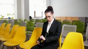 Concepto del asunto Una mujer se sienta en el centro de negocio y conseguir nerviosa antes de la entrevista Mirada de su muñeca a metrajes