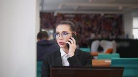 Concepto del asunto Una mujer se sienta la tabla y hablando en su tel?fono almacen de metraje de vídeo