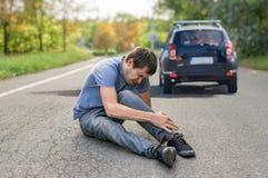 Concepto del atropello y fuga Hombre herido en el camino delante de un coche Imagenes de archivo