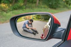 Concepto del atropello y fuga Opinión sobre hombre herido en el camino en espejo posterior de un coche foto de archivo