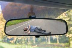 Concepto del atropello y fuga Opinión sobre hombre herido en el camino en espejo posterior de un coche fotos de archivo